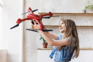Enfant tenant un drone rouge dans sa main