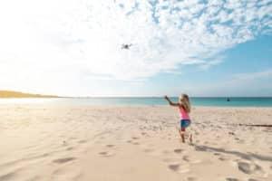 Enfant sur la plage avec un drone
